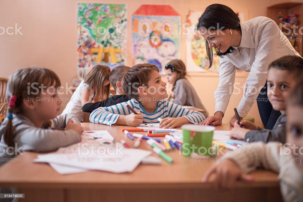 Smiling boy talking to his preschool teacher during art class. stock photo