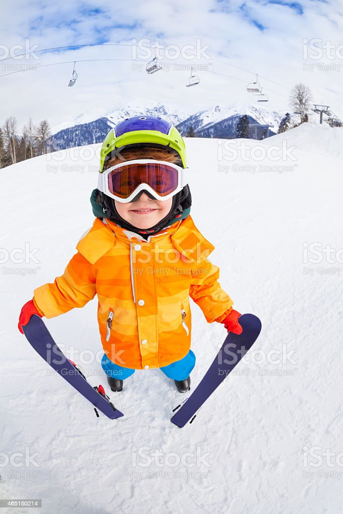 Smiling boy wearing mask holds ski in mountains stock photo