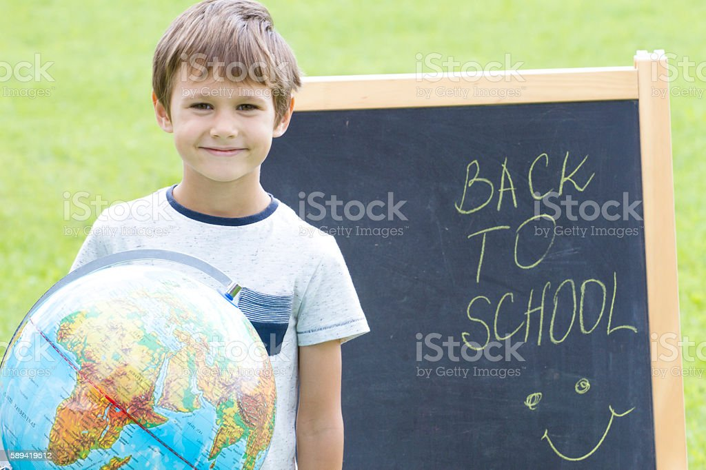 Smiling boy with a globe against the blackboard. Education Back stock photo