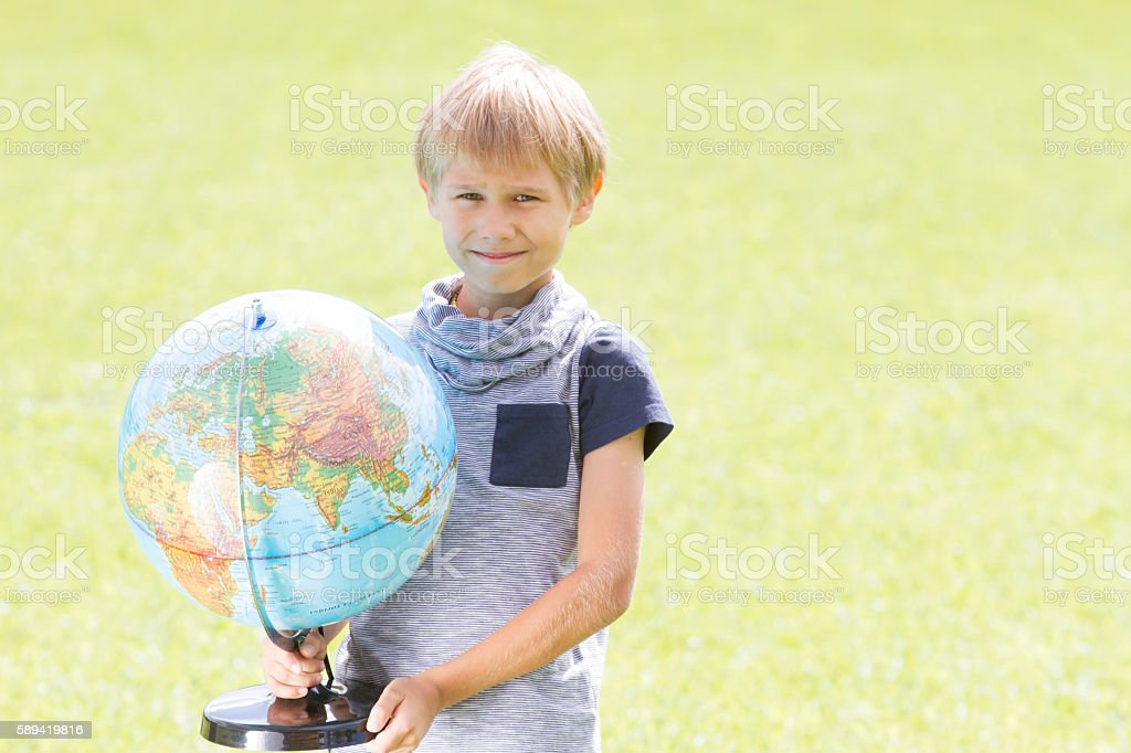Smiling boy with a globe outside. Education Back to school stock photo