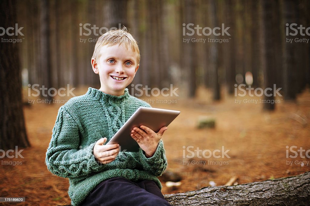 Smiling boy with digital tablet sitting on log in forest stock photo