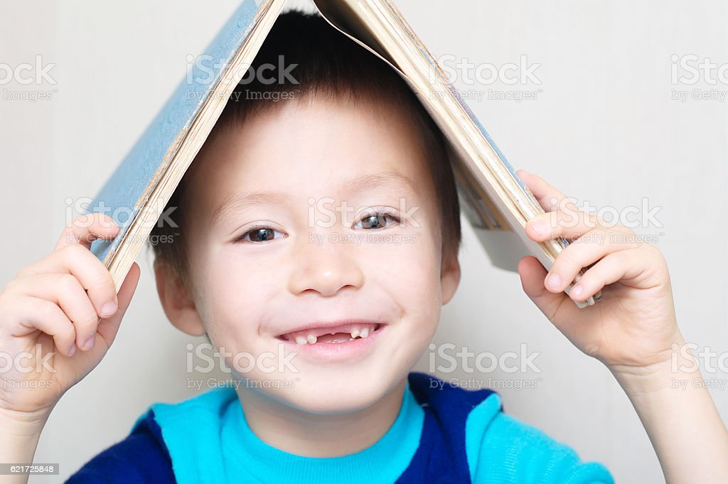 Smiling boy with dropped milk tooth with book stock photo