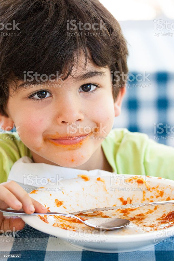 Smiling boy with empty plate stock photo