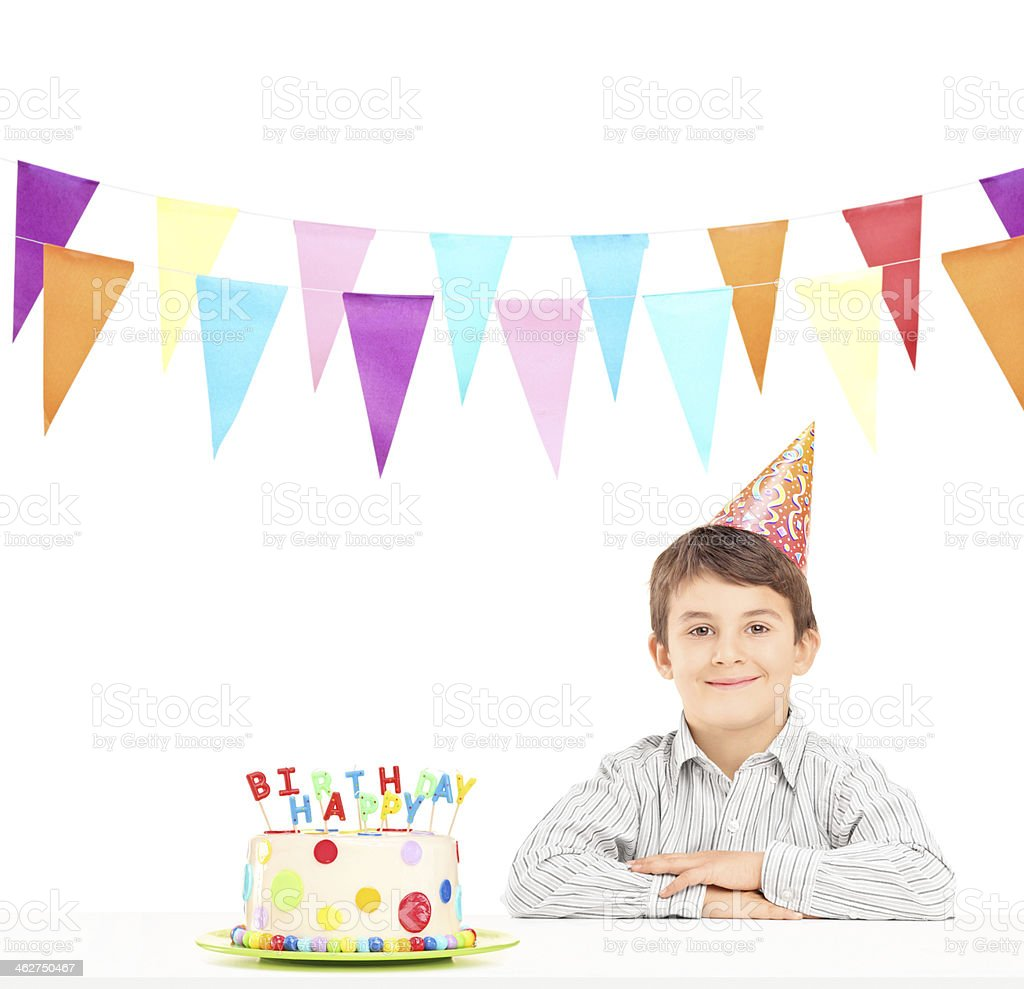 Smiling boy with party hat and a birthday cake stock photo