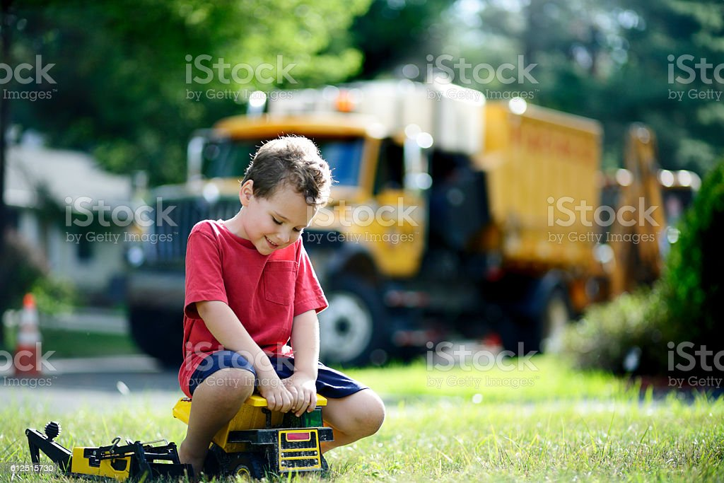 Smiling boy with special needs plays with his toy trucks stock photo