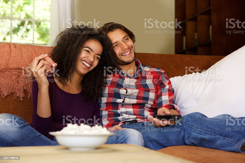 Smiling boyfriend and girlfriend relaxing watching tv stock photo