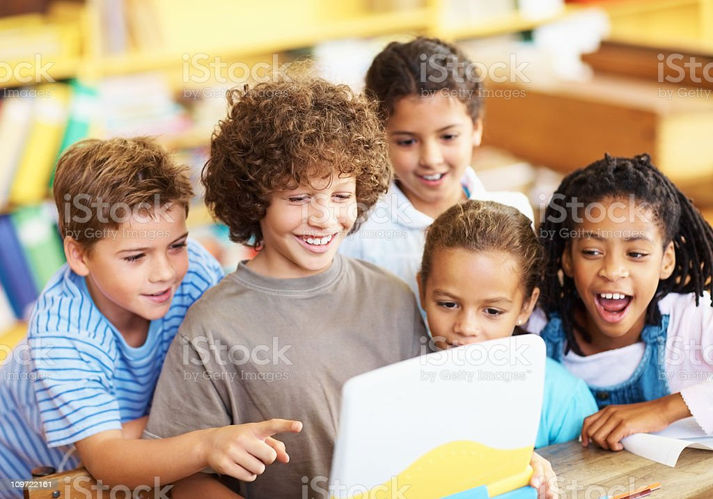 Smiling boys and girls looking at laptop royalty-free stock photo