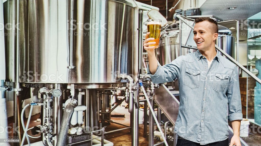 Smiling brewmaster holding a glass in industry stock photo