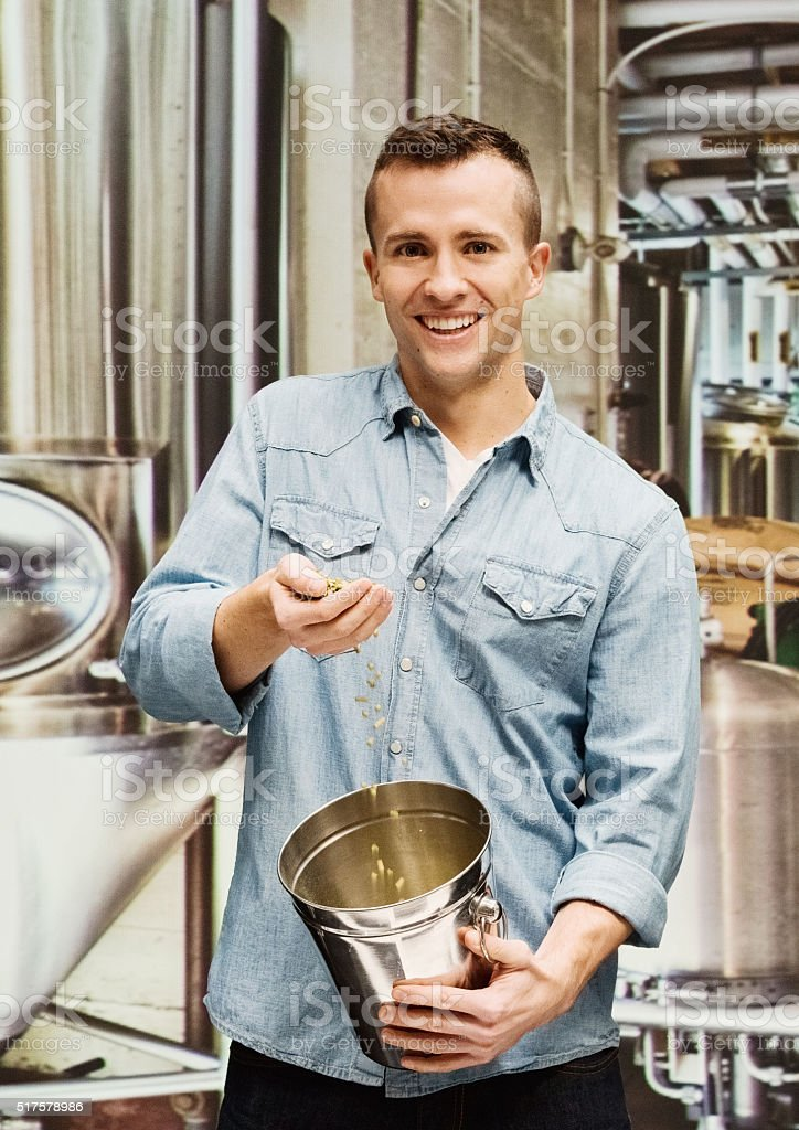 Smiling brewmaster holding bucket in brewery stock photo