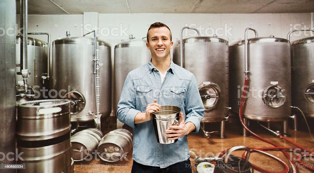 Smiling brewmaster holding glass in the industry stock photo