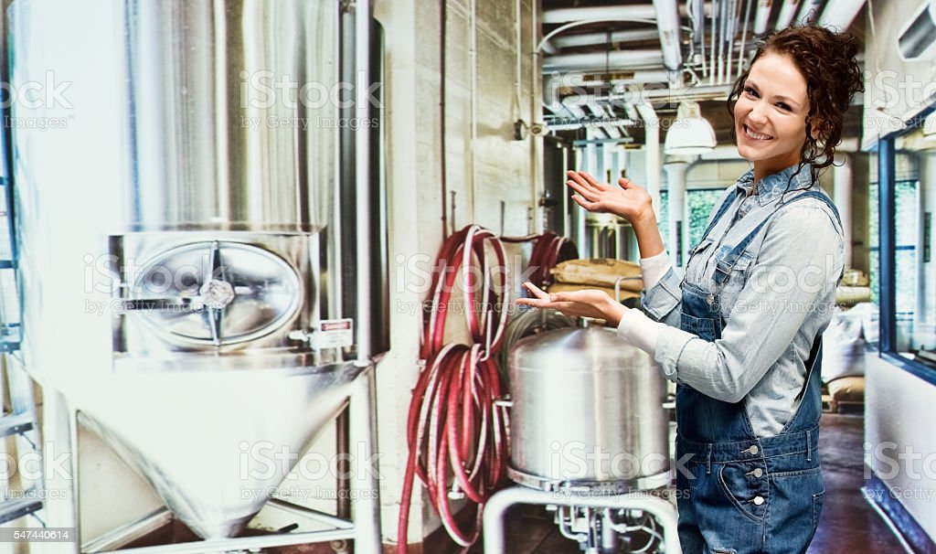 Smiling brewmaster presenting in brewery stock photo