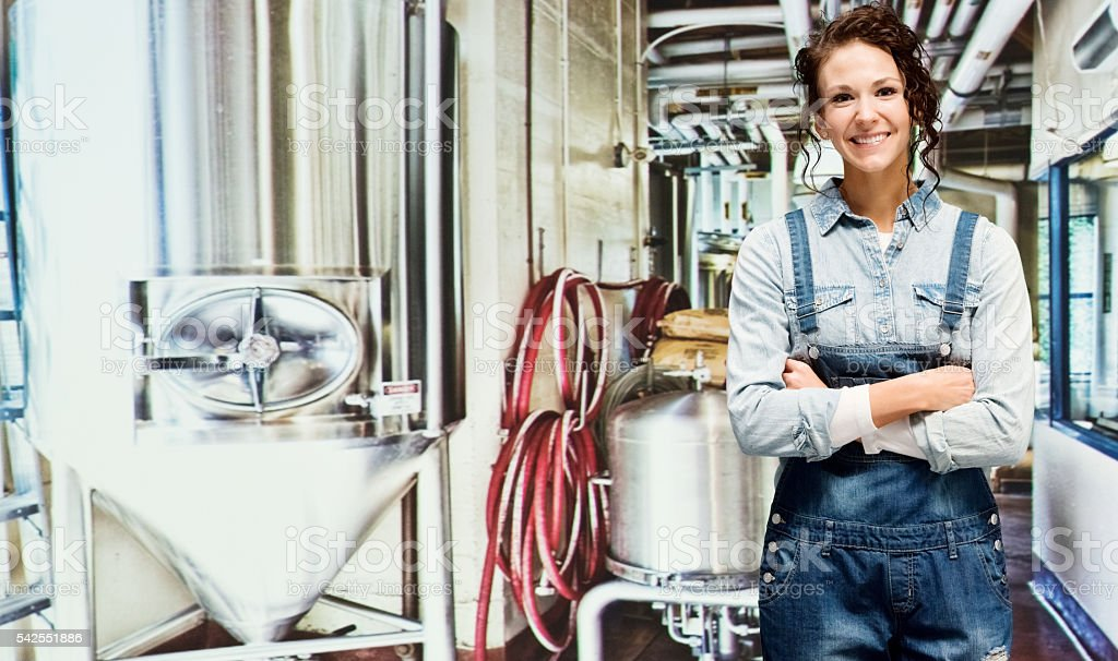 Smiling brewmaster standing in brewery stock photo