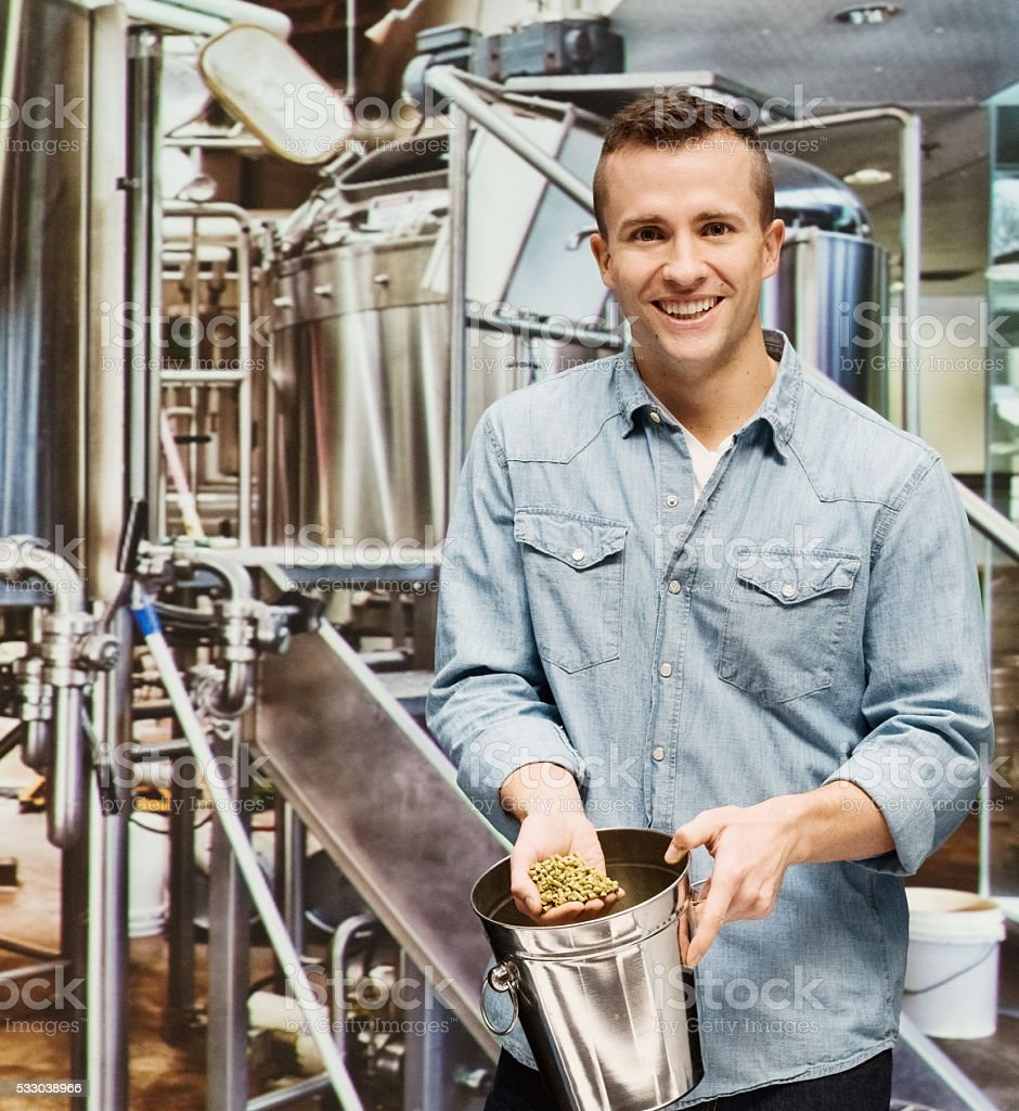 Smiling brewmaster working in brewery stock photo