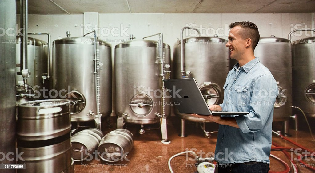 Smiling brewmaster working with laptop in industry stock photo