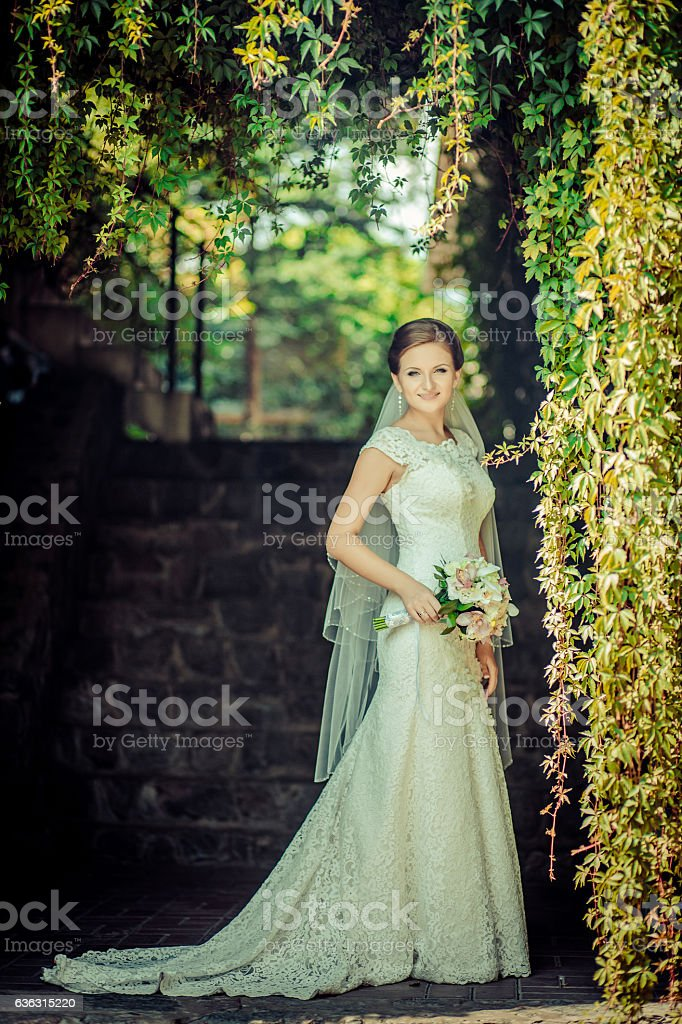 Smiling bride holding big wedding bouquet outdoor stock photo