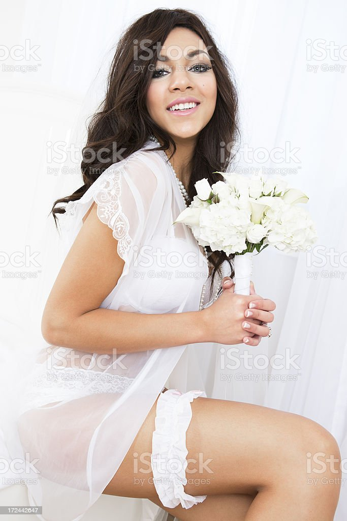 Smiling bride in lingerie sitting on bed royalty-free stock photo