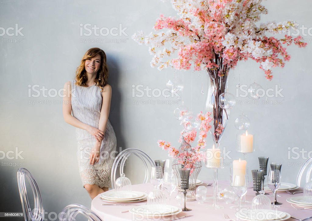 Smiling bride near the wall and wedding decorations stock photo