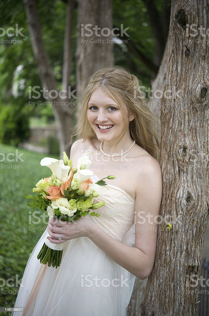 Smiling bride next to a tree stock photo
