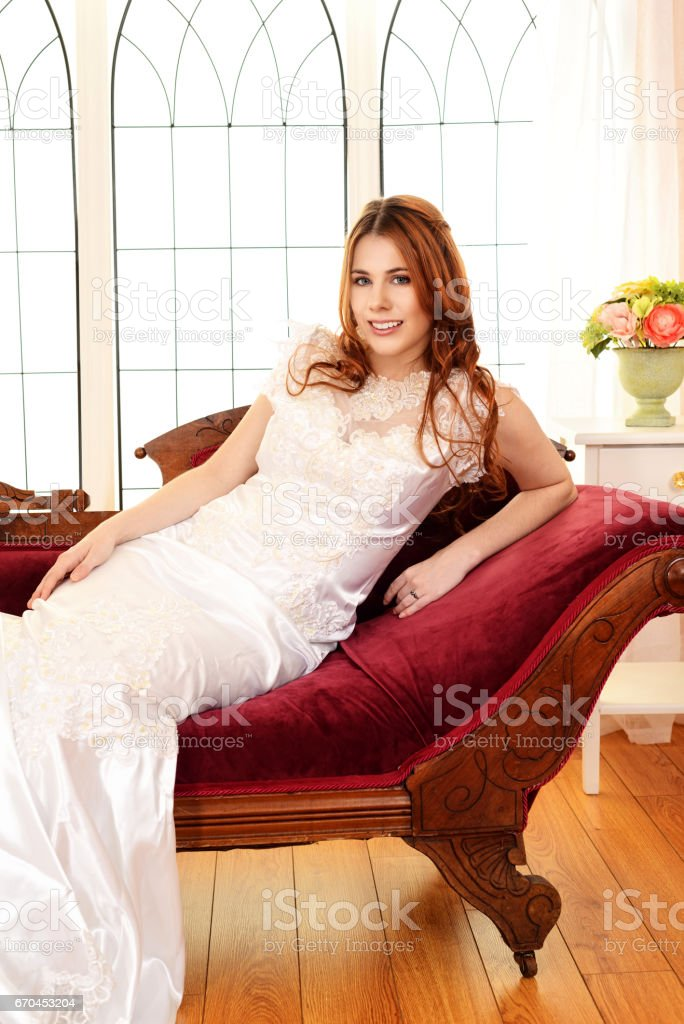 smiling bride sitting on victorian couch stock photo