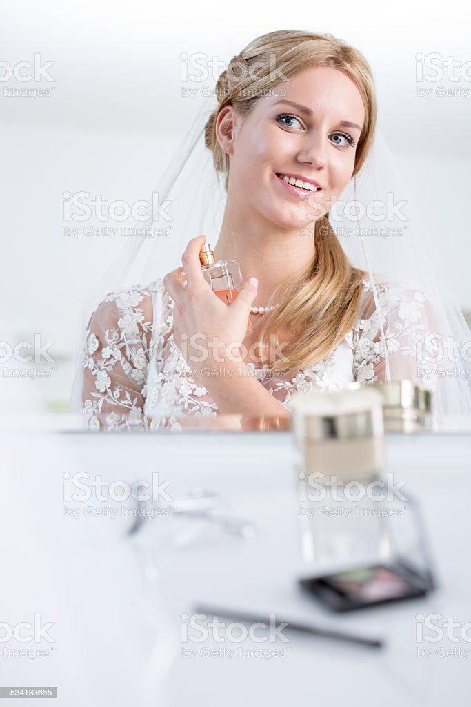 Smiling bride using perfume stock photo