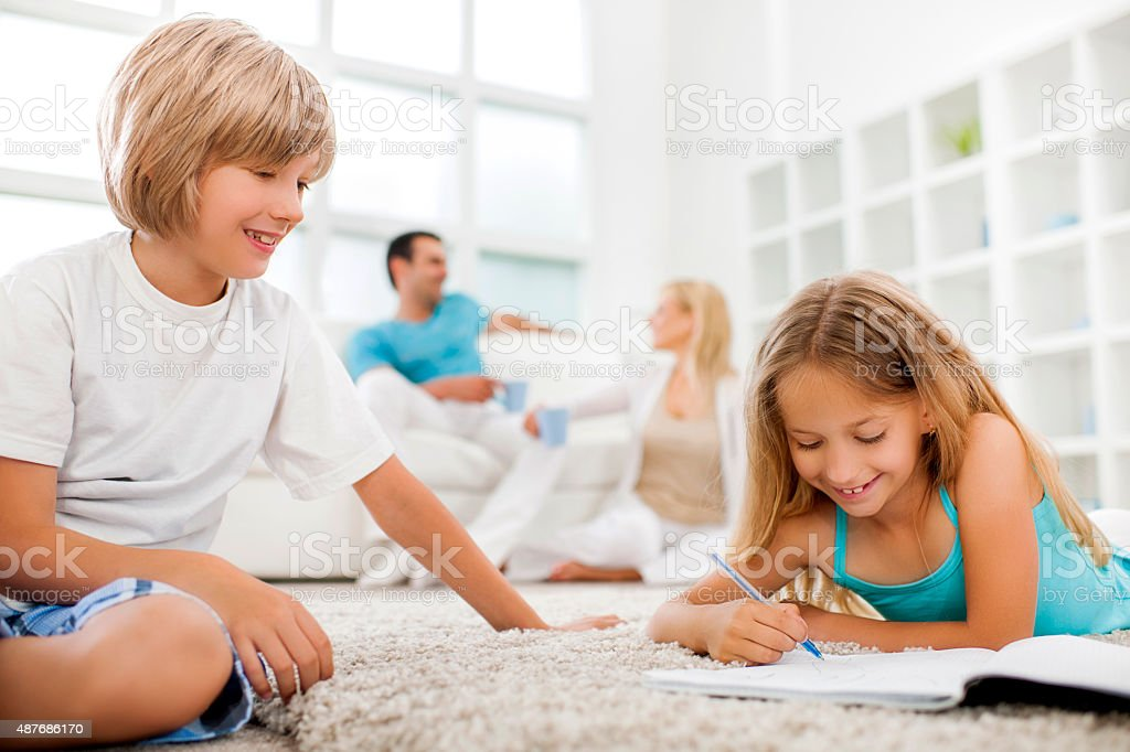 Smiling brother and sister writing at home. stock photo
