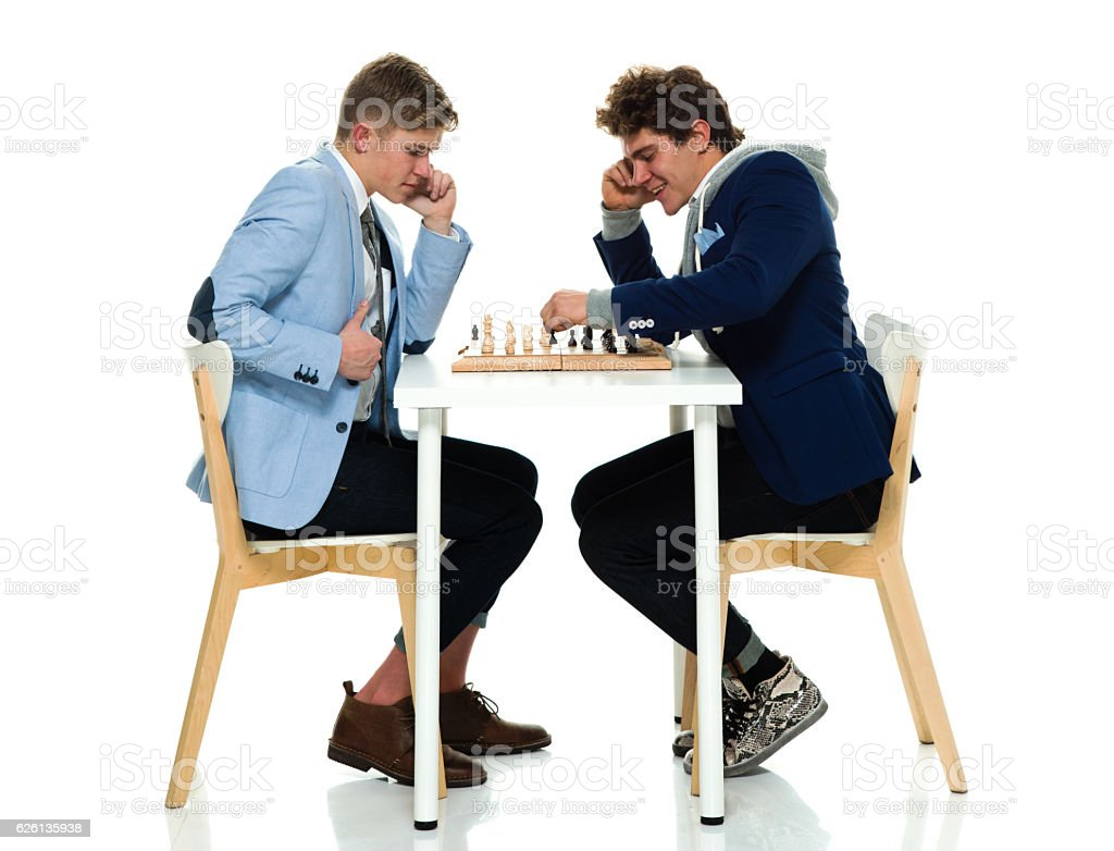 Smiling brothers playing chess stock photo