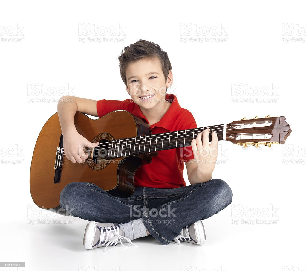 A smiling brown haired boy plays an acoustic guitar  stock photo