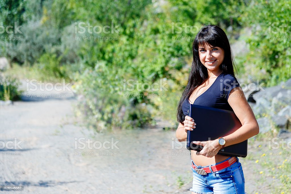 smiling brunette girl with long hair holding laptop outdoors stock photo