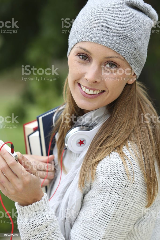 Smiling brunette student holding books and smartphone royalty-free stock photo