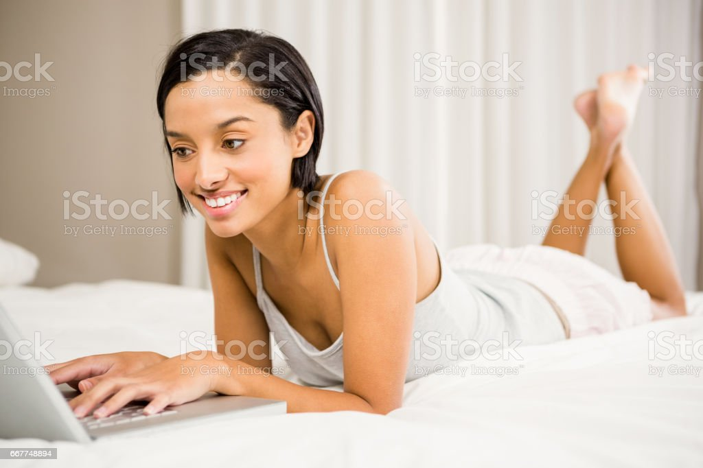 Smiling brunette using laptop royalty-free stock photo