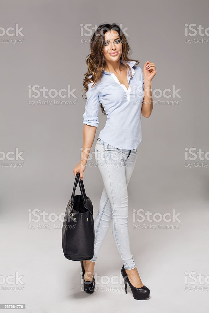 Smiling brunette woman holding a bag. Isolated on grey backgroun stock photo
