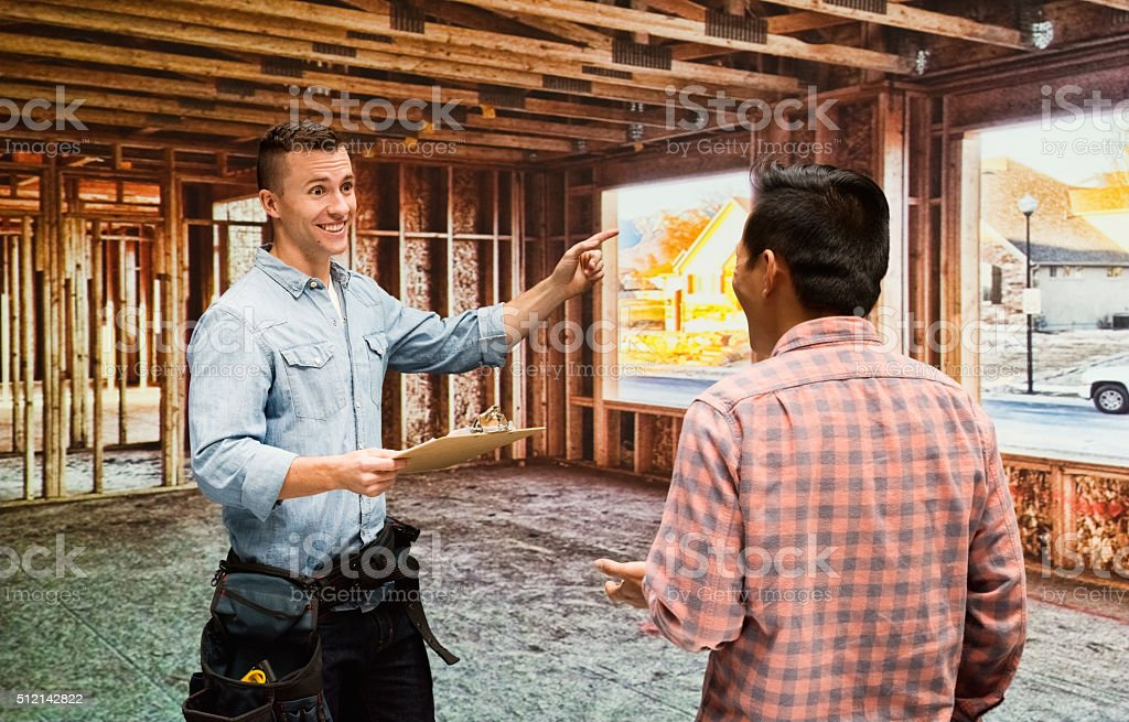 Smiling building contractor discussion and pointing stock photo