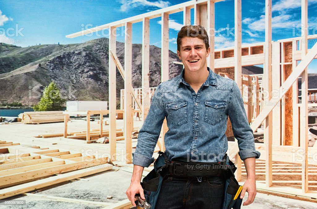 Smiling building contractor in construction site stock photo