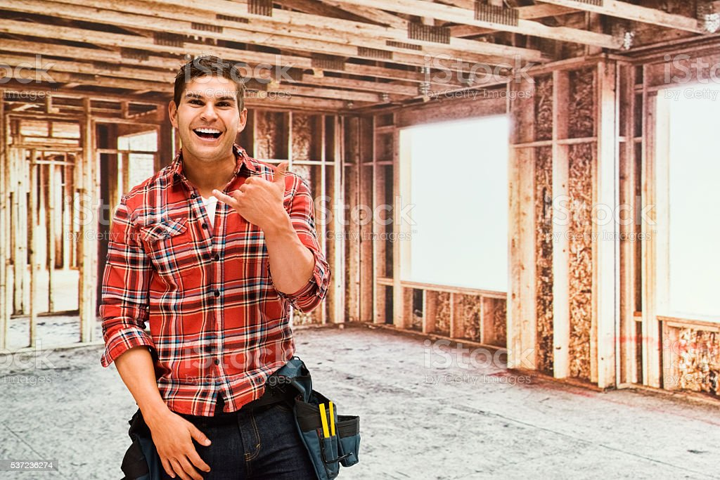 Smiling building contractor showing shaka sign stock photo