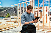 Smiling building contractor using tablet outdoors