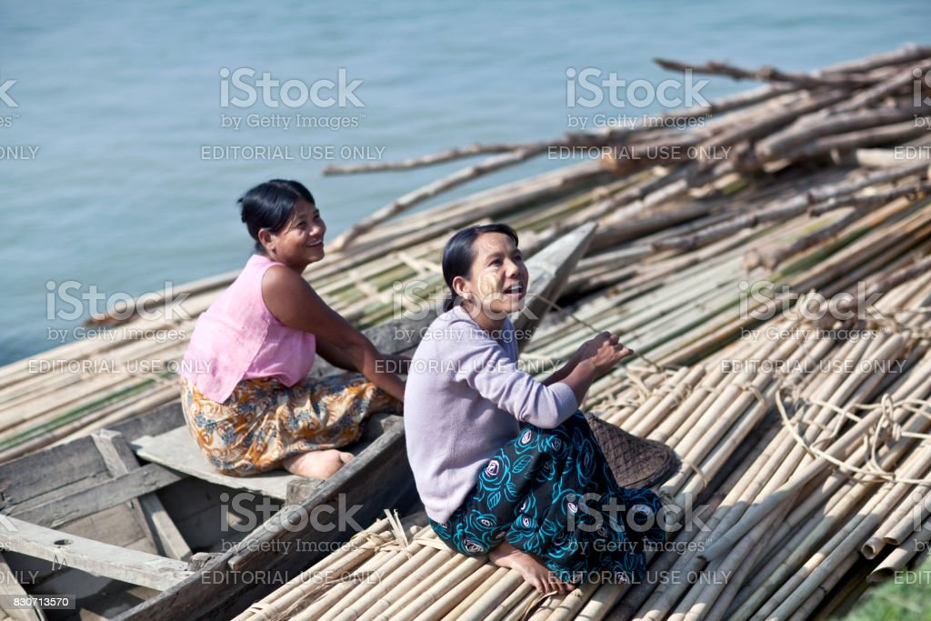 Smiling Burmese women traveling by wooden boat on Irrawaddy river stock photo