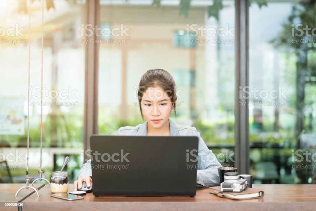 Smiling business asian woman used laptop and smart phone in coffee shop,business concept. stock photo
