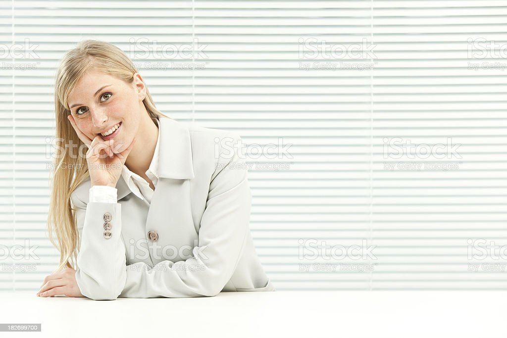 smiling business blond girl near venetian blind window royalty-free stock photo