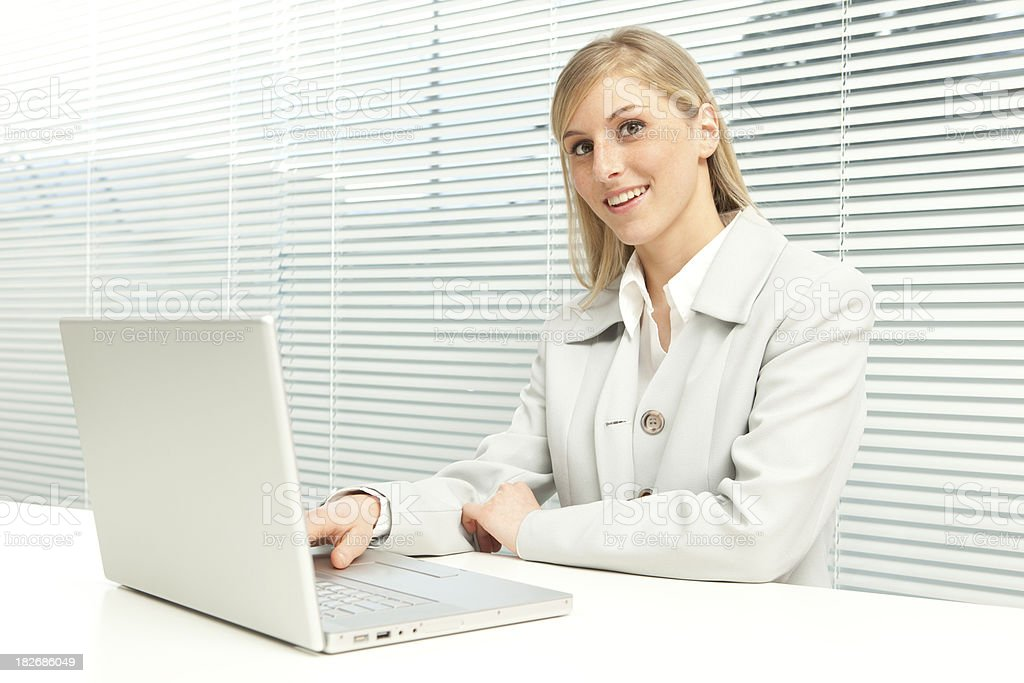 smiling business blond girl with laptop near venetian blind window royalty-free stock photo