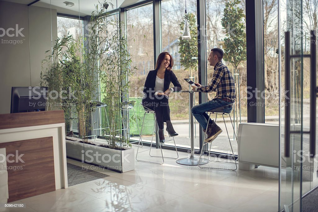 Smiling business colleagues sitting in entrance hall and communicating. stock photo