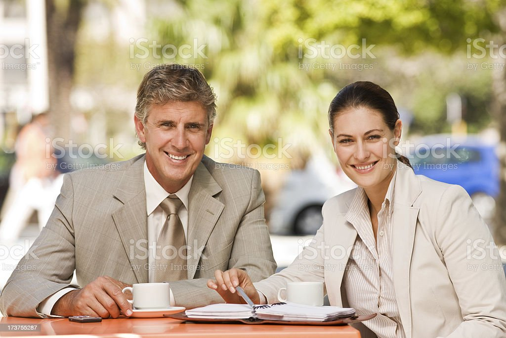 Smiling business colleagues sitting together with documents and coffee royalty-free stock photo