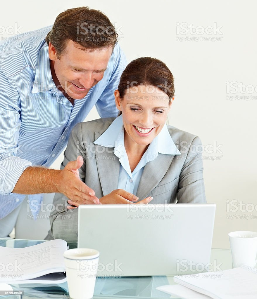 Smiling business colleagues using a laptop royalty-free stock photo