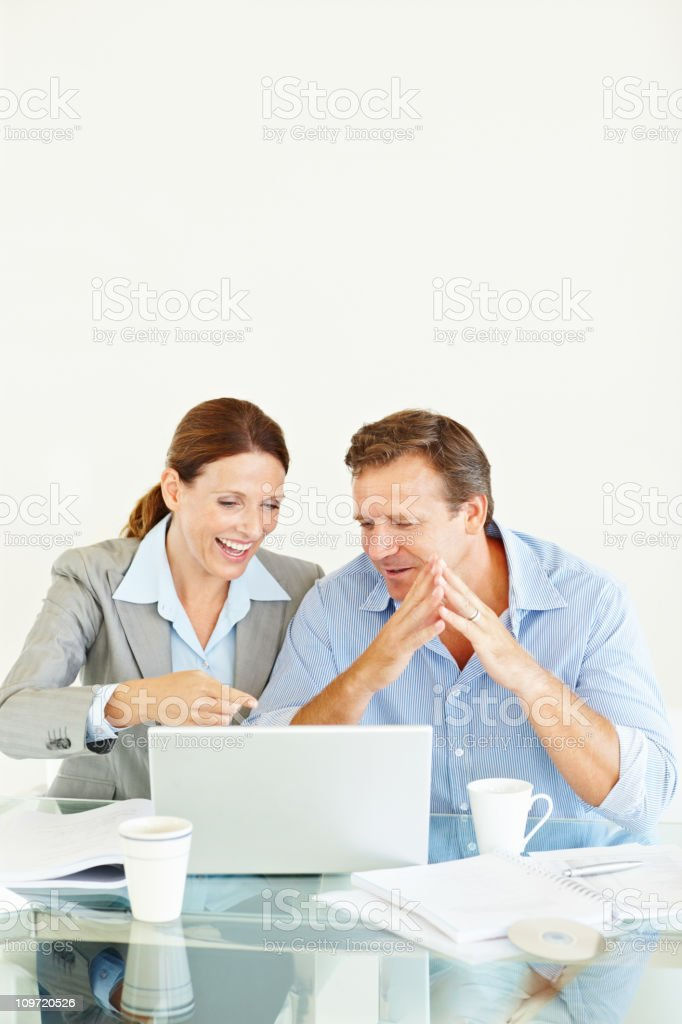Smiling business colleagues working on a laptop royalty-free stock photo