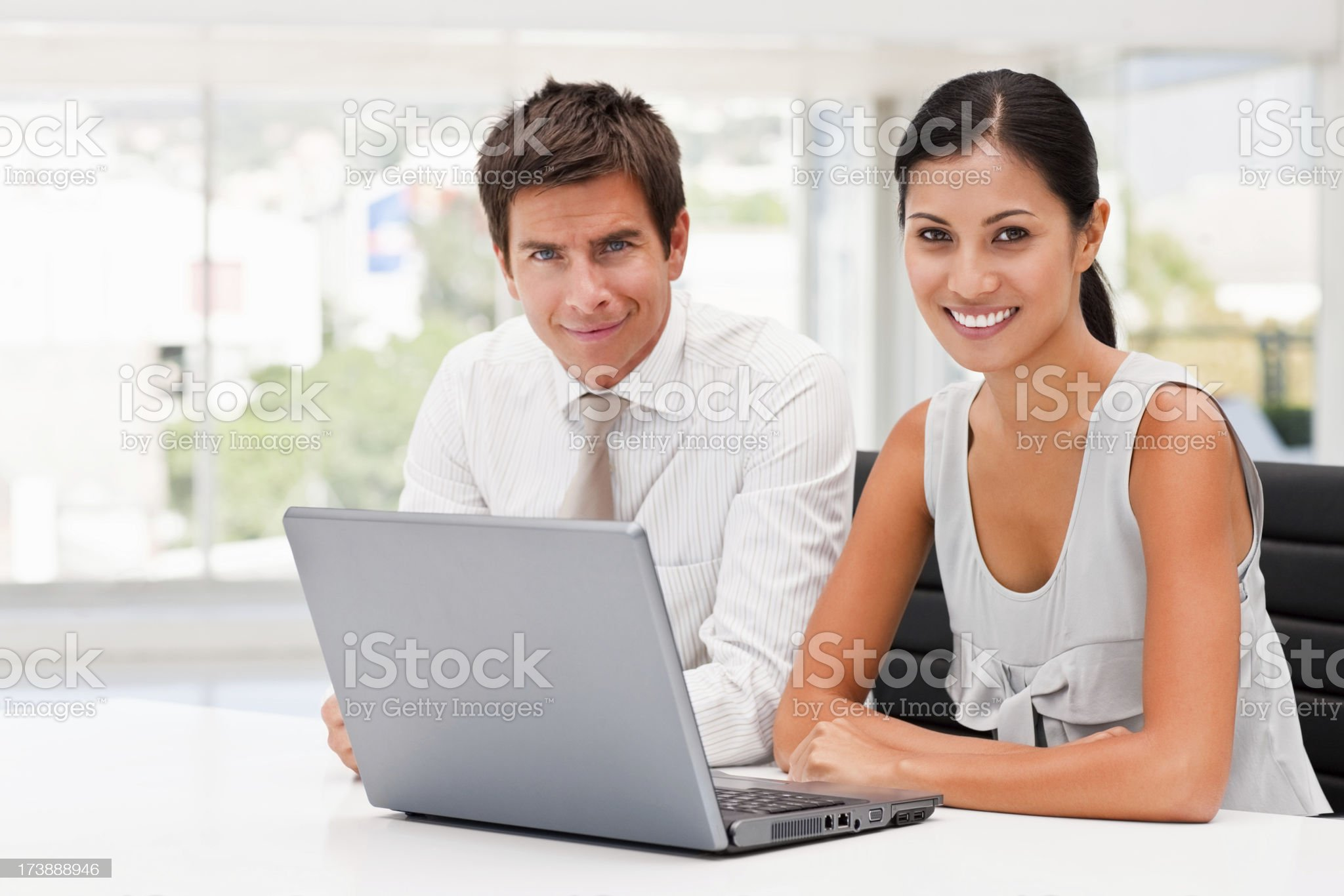Smiling business colleagues working on laptop royalty-free stock photo