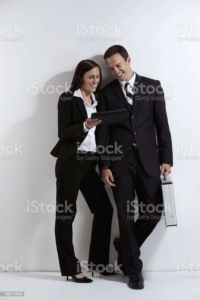 Smiling business couple looking at a digital tablet royalty-free stock photo