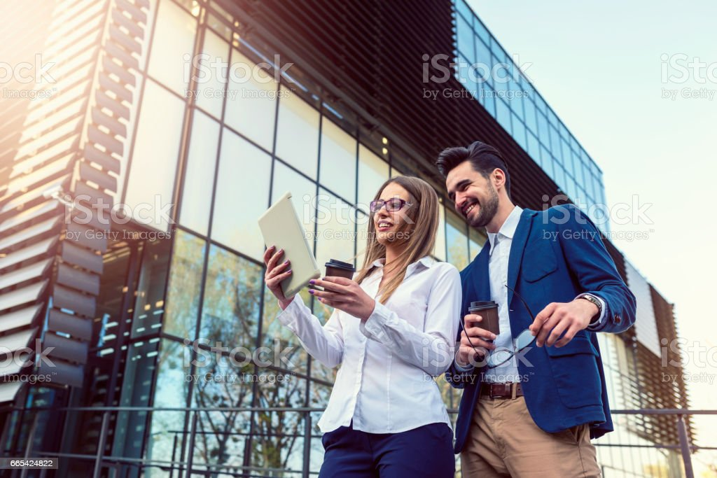 Smiling business couple outdoors in the street on coffee brake stock photo