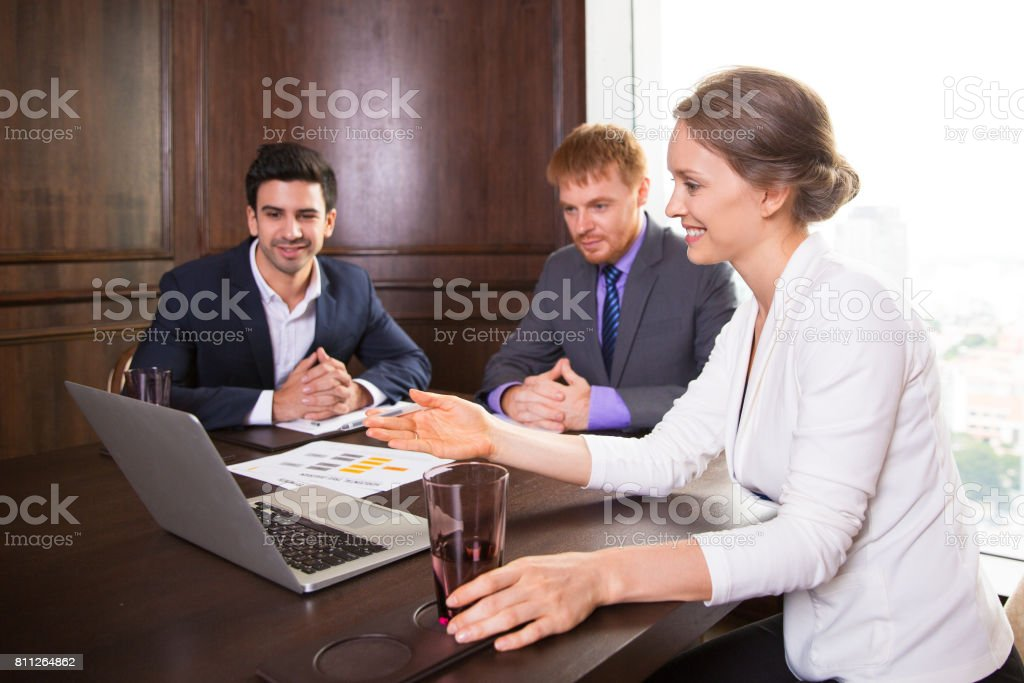 Smiling business lady showing presentation to colleagues stock photo