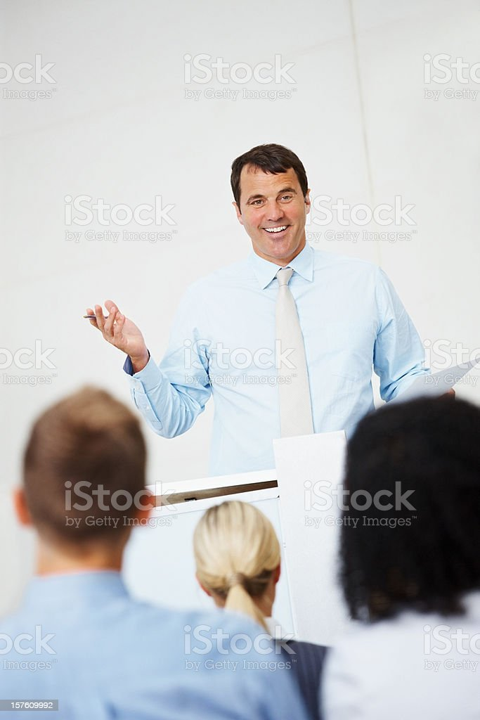 Smiling business man addressing a group of people royalty-free stock photo