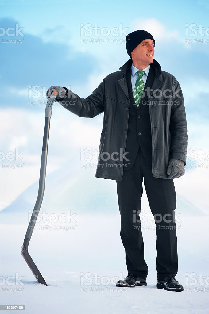 Smiling business man in front of snow pile with shovel stock photo