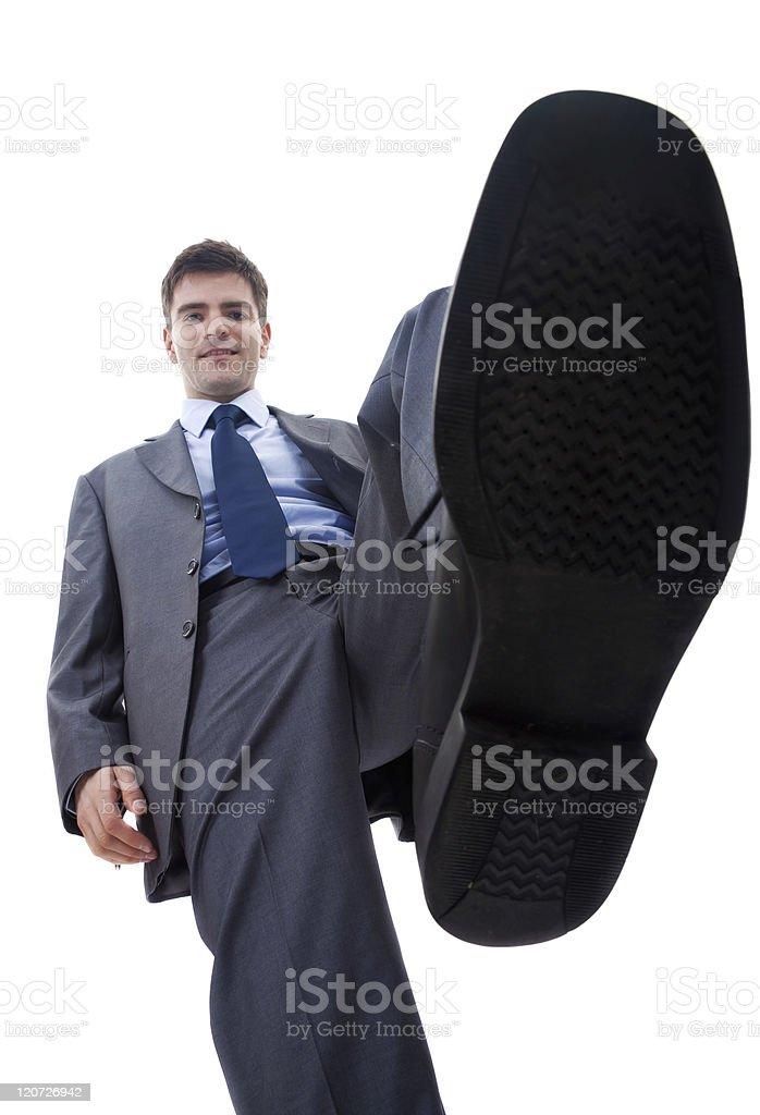 smiling business man steping on something stock photo